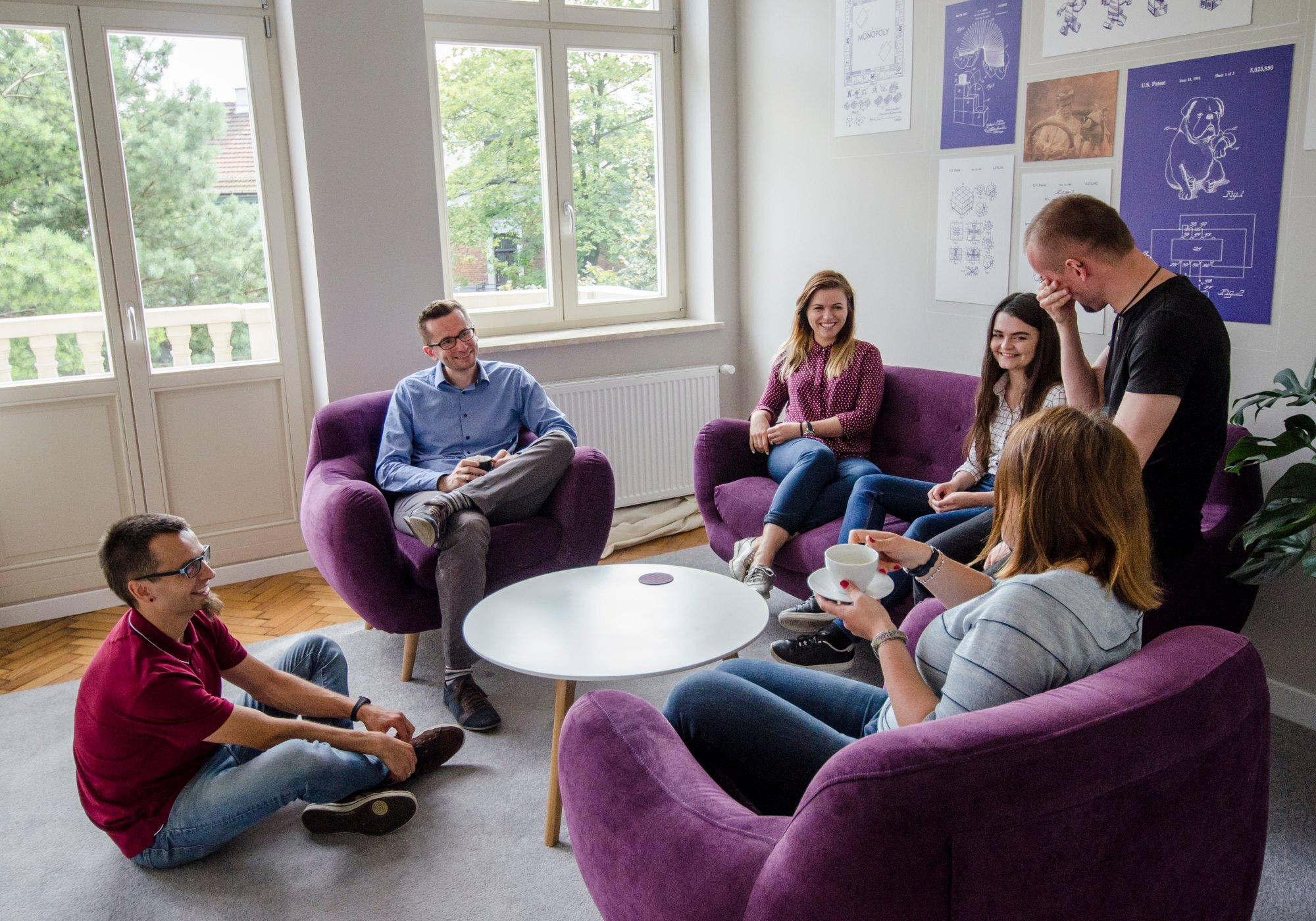 people sitting on armchairs and a couch, talking lively, lauching hard
