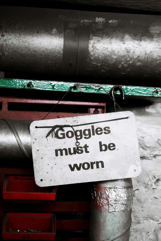 A picture showing a 'Googles must be worn' plate on a machine