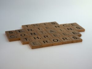 A sentence made of scrabble tiles with three errors.
